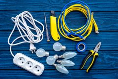 Working with electrical equipment. Bulbs, pilers, screwdriver on blue wooden background top view copy space. Working with electrical equipment. Bulbs, pilers royalty free stock image