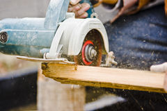 Working with electronic saw. Picture of a pair of hands working and cutting a wood board with an electronic saw Stock Photos
