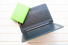 Working environment Netbook with a notebook are on the table. Next is a red apple royalty free stock photography