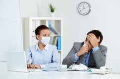 Working during epidemy. Image of sick businessman with tissue looking at laptop screen with his colleague in mask sitting near by in office royalty free stock photography
