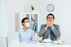 Working during epidemy. Image of sick businessman with tissue sneezing with his colleague in mask sitting near by in office royalty free stock image
