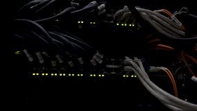 Working Ethernet switch in a dark data center room. Many flashing green lamps stock video