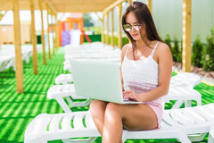 Working even on vacation. Attractive young woman in sunglasses and hat is lying on a chaise-longue near swimming pool with laptop. Attractive young woman in Royalty Free Stock Photography