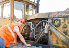 Working  examining bulldozer engine Stock Photo