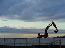 Working excavator against the evening sky. And the city on the horizon Royalty Free Stock Image