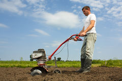 Working farmer. Man using cultivator or rotovator to till soil in a rural setting Stock Photography