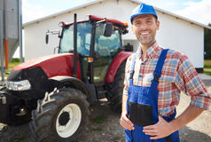 Working farmer. Man in unform and farm in the background Royalty Free Stock Images