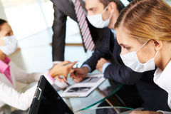 Working female. Serious businesswoman in protective mask looking at screen of laptop in working environment stock photo