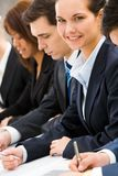 Working female. Confident businesswoman looking at camera among her colleagues at briefing stock image