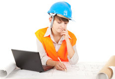Working female architect with blueprint and laptop Stock Photo