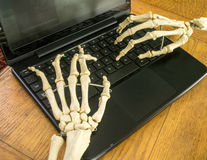 Working fingers to the bone. Skeleton hands and fingers work at a computer Stock Images