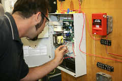 Working on Fire Alarm. A student electrician wiring a fire alarm system at his technical college royalty free stock images