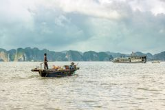 Working on fishing boat. QUANG NINH- VIETNAM: man and woman working on fishing boat in Ha Long bay, Quang Ninh province, Vietnam. Ha Long Bay is recognized as a Royalty Free Stock Photography