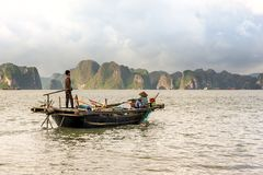 Working on fishing boat. QUANG NINH- VIETNAM: man and woman working on fishing boat in Ha Long bay, Quang Ninh province, Vietnam. Ha Long Bay is recognized as a Stock Photo