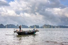 Working on fishing boat. QUANG NINH- VIETNAM: man and woman working on fishing boat in Ha Long bay, Quang Ninh province, Vietnam. Ha Long Bay is recognized as a Royalty Free Stock Photos