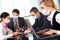 Working during flu epidemy. Serious businesswoman in protective mask looking at screen of laptop in working environment Stock Images