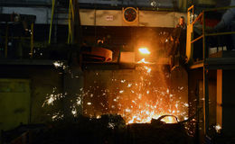 Working in a foundry. Workers looking down, red color is a reflection of the molten metal Royalty Free Stock Images