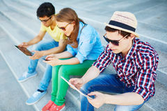 Working with gadgets. Modern teenagers sitting on stairs at leisure and using gadgets Stock Photo
