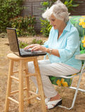 Working In The Garden. A senior woman using a laptop computer in her garden Stock Photo