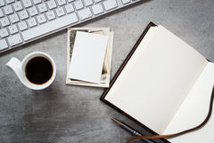 Working with genealogy. A blank notebook, computer keyboard, vintage photos and a cup of coffee royalty free stock photography