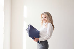 Working girl blonde with blue folders. In hands Royalty Free Stock Images