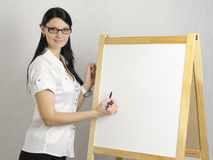 Business woman writes on a white board marker. Working Girl in glasses writes a marker on a white board, looking at the camera. Studio, white background Royalty Free Stock Photography