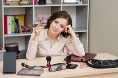 Working Girl makeup laid on the table. Young woman sitting at office table, laid out on the table cosmetics Royalty Free Stock Image