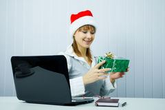 Working Girl in Santa hat with a gift Stock Photos
