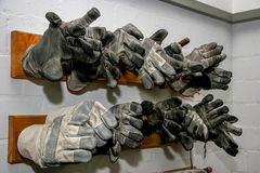 Working gloves at the wall. Working protective gloves in wardrobe on the wall. Firefighters gloves at the wall stock photo