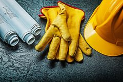 Working gloves with yellow helmet and rolled blueprints royalty free stock photos