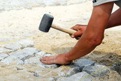 Working with the granite sett. Man placing the granite sett, cobblestone stock photography