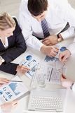 Working with graphs. Above view of businesspeople discussing graphs Royalty Free Stock Image