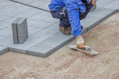 Working on gravel flattening before lay patio pavers Stock Image