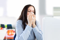 Working with a great cold. Businesswoman with a cold at the office Stock Photography