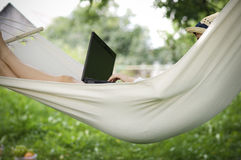 Working on hammock with laptop Stock Images
