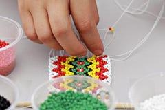 Working hand: demonstrating bead works of Kadazandusun beading c Royalty Free Stock Images