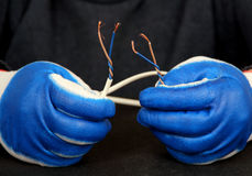 Electrical wire in his hands. Royalty Free Stock Photos