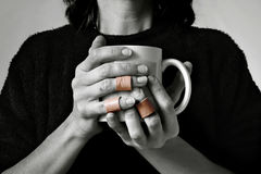 Working Hands. A women holding a coffee cup with bandaged fingers. The image is black and white and the bandages are natural color Stock Images