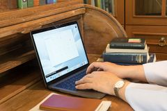 Working Hands on Laptop with surrounding books on antique wooden desk. Male hands working with laptop on wooden classic desk surrounding with books besides Stock Photo