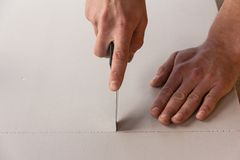Working hands. The man cuts the knife polystyrene sheet Stock Images
