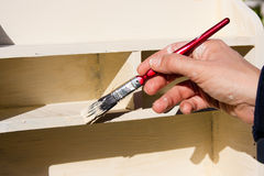 Working Hands Painting Shelves in Sunshine Stock Photo