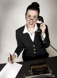 Working Hard. Retro office worker with vintage typewriter and phone answering a call stock image