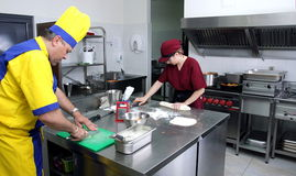 Working hard. Two cooks preparing delicious pastry Royalty Free Stock Photos
