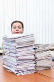 Working hard and long. Head of young caucasian woman behind pile from project drawings blueprints stock photo