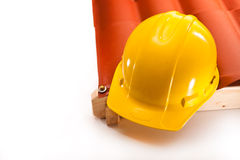 Working at heights requiring uniforms. Working yellow hardhat on the edge of the roof on a white background Stock Photo