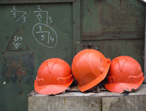 Working helmets. Against an iron wall with working records Royalty Free Stock Photography