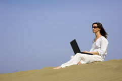 Working holiday1. Girl working on her laptop in the dunes in Gran Canaria royalty free stock image