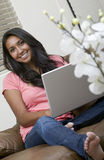 Working from home. A beautiful woman working on her computer while relaxing on the couch Royalty Free Stock Image