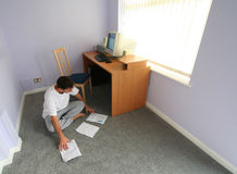 Working at home. Man working at home sitting on carpet stock photography