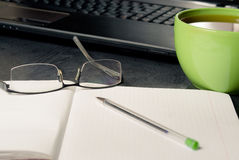 Working from home. A laptop with tea cup, notepad, glasses and pen Royalty Free Stock Photography